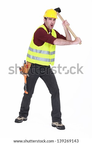 Construction worker smashing with a sledgehammer - stock photo