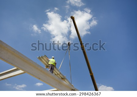 Construction worker standing on concrete beam on height and placing roof materials lifted by crane - stock photo