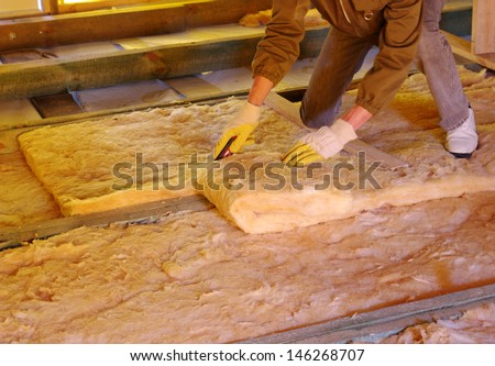Construction worker thermally insulating house attic with glass wool  - stock photo