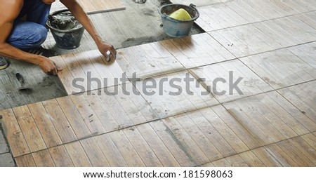 Construction worker tiling the floor. - stock photo