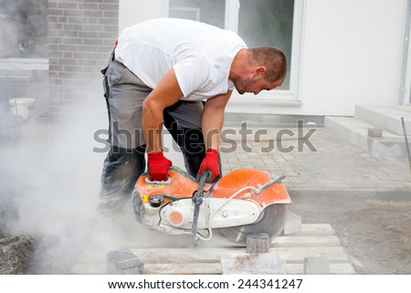 Construction worker using a concrete saw, cutting stones in a cloud of concrete dust for creating a track. - stock photo