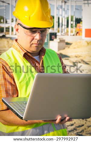 Construction Worker Using Laptop - stock photo
