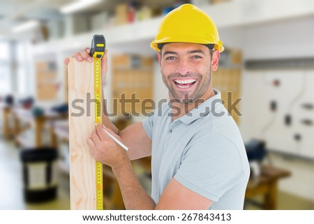 Construction worker using measure tape to mark on plank against workshop - stock photo