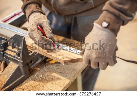 Construction Worker Using Tape Measure. Professional carpenter at work measuring wooden planks - stock photo