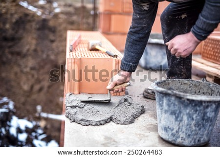 Construction worker using trowel and cement for installing the brickwork - stock photo