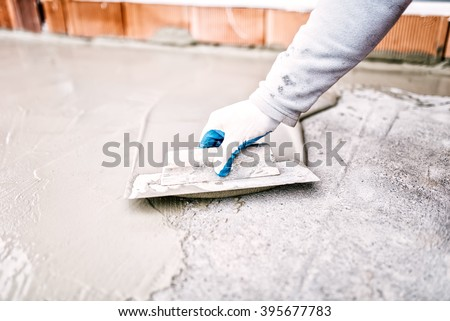 construction worker using trowel and mason's float for hydroisolating and waterproofing house - stock photo