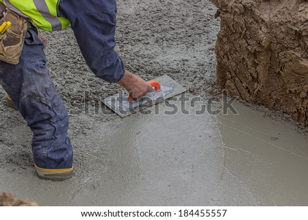 Construction worker using trowel to finish top of foundation to the desired smoothness using a hand trowel - stock photo