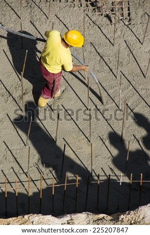 Construction worker vibrating concrete foundations of hydro power plant - stock photo