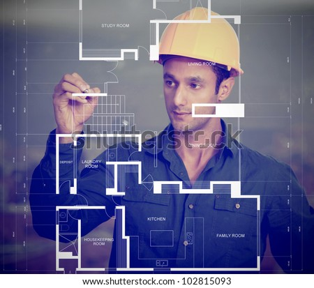 Construction worker wearing a helmet and sketching blueprints - stock photo