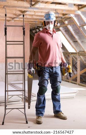 Construction worker wearing protective mask and holding tools in attic - stock photo