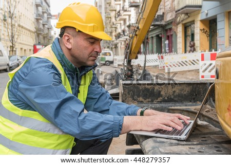 Construction worker wearing safety jacket and yellow hardhat using tablet computer. Outdoors - stock photo