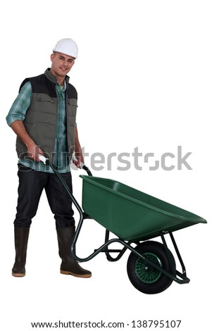 Construction worker with a wheelbarrow - stock photo
