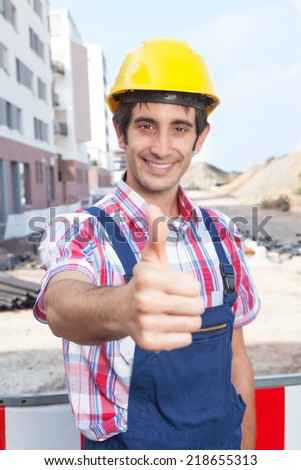 Construction worker with black hair showing thumb up - stock photo