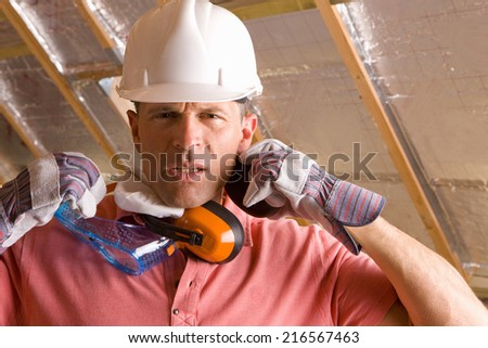 Construction worker with hard hat, goggles and ear protectors - stock photo