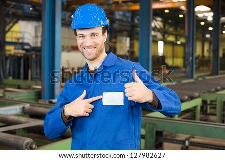 Construction worker with helmet in assembly hall with thumbs up - stock photo