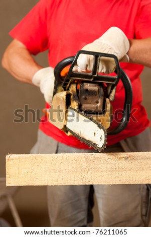 Construction worker with motor saw doing some renovation - stock photo