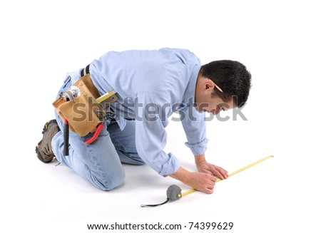 Construction worker with tool belt measuring the floor over white background - a series of MANUAL WORKER images. - stock photo