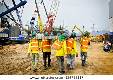 Construction workers are bearing wood, to be unity - stock photo