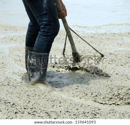Construction workers are using the newly poured cement spreaders of crane into the ground  - stock photo