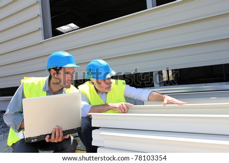 Construction workers checking building material - stock photo