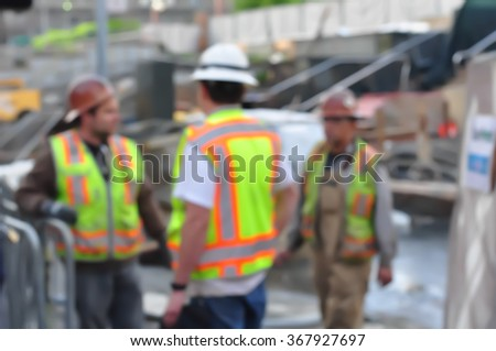 Construction workers conversing at building/construction site - stock photo