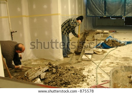 Construction workers digging up cement - stock photo