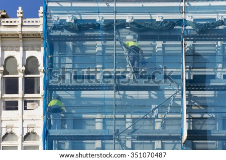 construction workers in  scaffolding  on the building  facade for restore, repair and renovate - stock photo