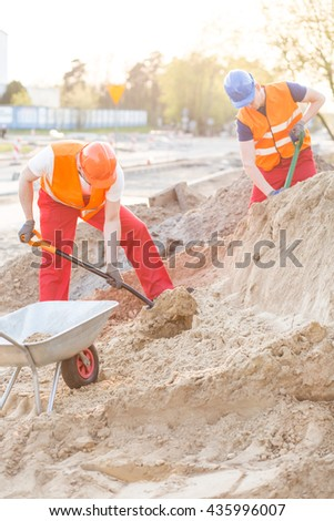 Construction workers loading the sand with shovels - stock photo