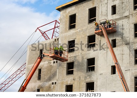 Construction workers on scaffolding platforms - stock photo