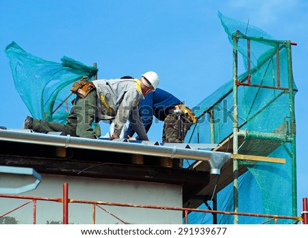 Construction workers on the roof - stock photo