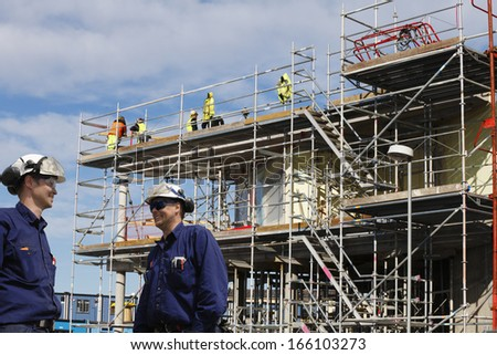 construction workers, scaffolding and building-site - stock photo