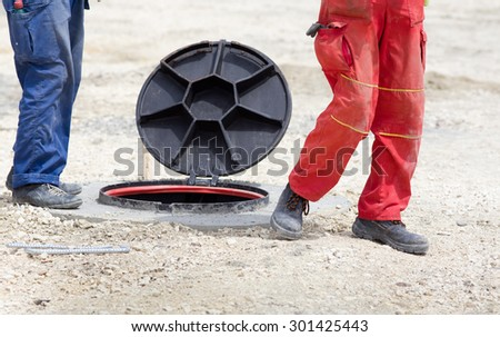 Construction workers standing beside manhole with open cover at building site - stock photo