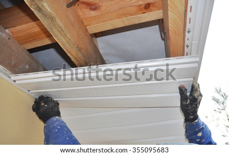 Constructor Install Soffit. Roofing Construction. Soffit and Fascia is Usually Constructed of Vinyl, Wood or Aluminum and is Installed on the Underside of Roof Overhangs and Eaves. - stock photo