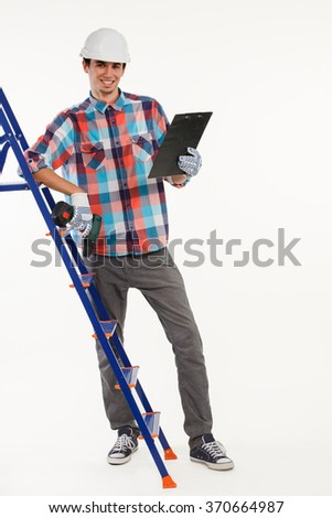 Constructor with hand drill on ladder. Young man in hardhat on white background. Housebuilder with clipboard standing at ladder. - stock photo