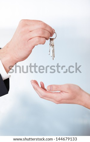 Consultant Giving Keys To Woman In Office - stock photo