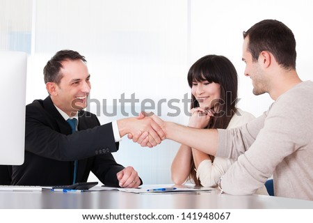 Consultant Shaking Hands With A Man In Office - stock photo