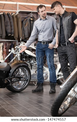Consulting customer. Young cheerful young sales executive consulting customer about motorcycle - stock photo