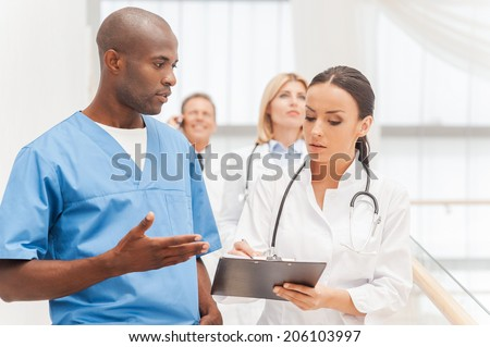 Consulting on the go. Group of confident doctors moving downstairs while two of them discussing something and gesturing - stock photo