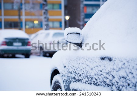 Consumer car covered by snow in a winter day. - stock photo