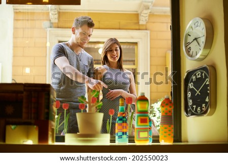 Consumerism and modern life-Happy people with man and woman shopping in retail shop, standing near store window - stock photo