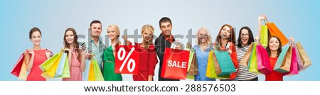 consumerism, people and discount concept - group of happy people with percentage and sale sign on shopping bags over blue background - stock photo