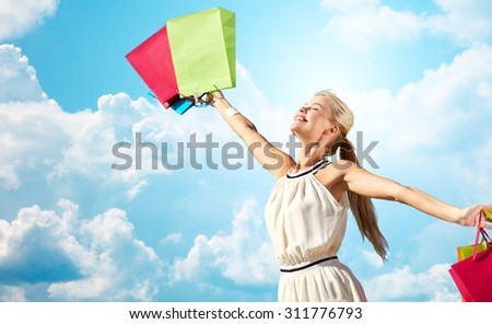 consumerism, sale and people concept - smiling woman with shopping bag rising hands over blue sky and clouds background - stock photo