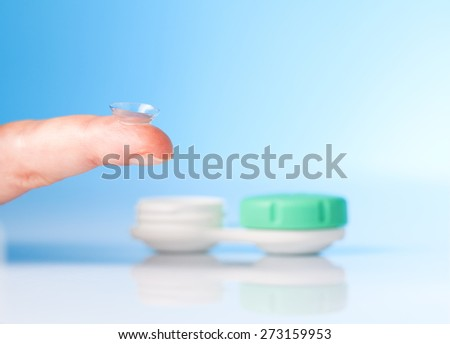 contact lens on finger and case on blue background - stock photo