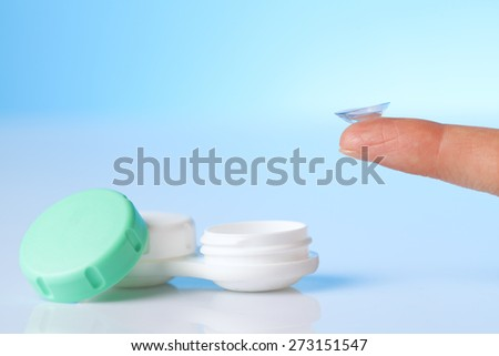 contact lens on finger and protaction case - stock photo