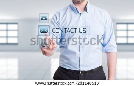 Contact options in digital futuristic concept with hand pressing button on transparent digital screen - stock photo