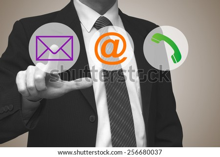 Contact us concept, businessman pressing contact button on virtual screen - stock photo