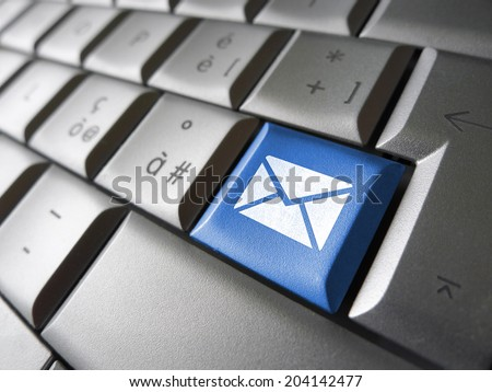 Contact us Internet concept with e-mail icon and symbol on a blue laptop computer key for website, blog and on line business. - stock photo