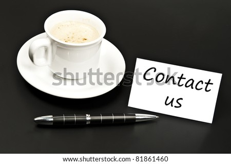 Contact us noted on desk with coffee - stock photo