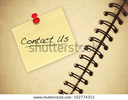contact us post it on the book - stock photo
