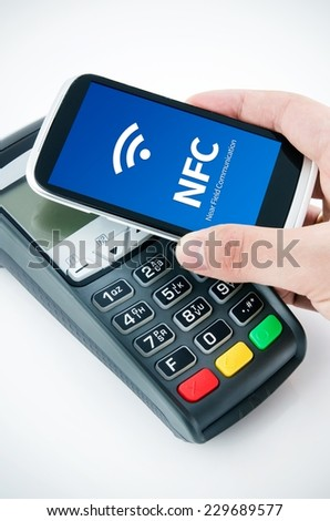 Contactless payment card with NFC chip in smart phone - stock photo